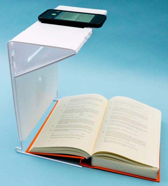 A smartphone with KNFB Reader on the portable stand above an open book