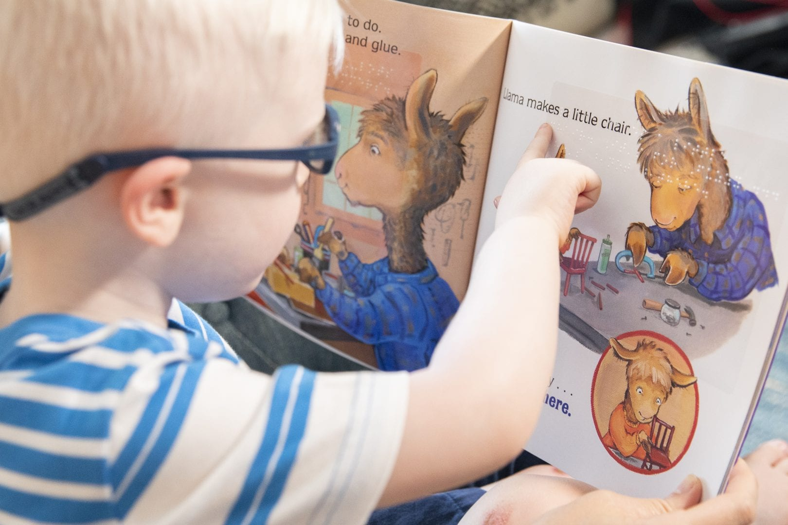a young boy in glasses touching the braille in a Llama Llama book