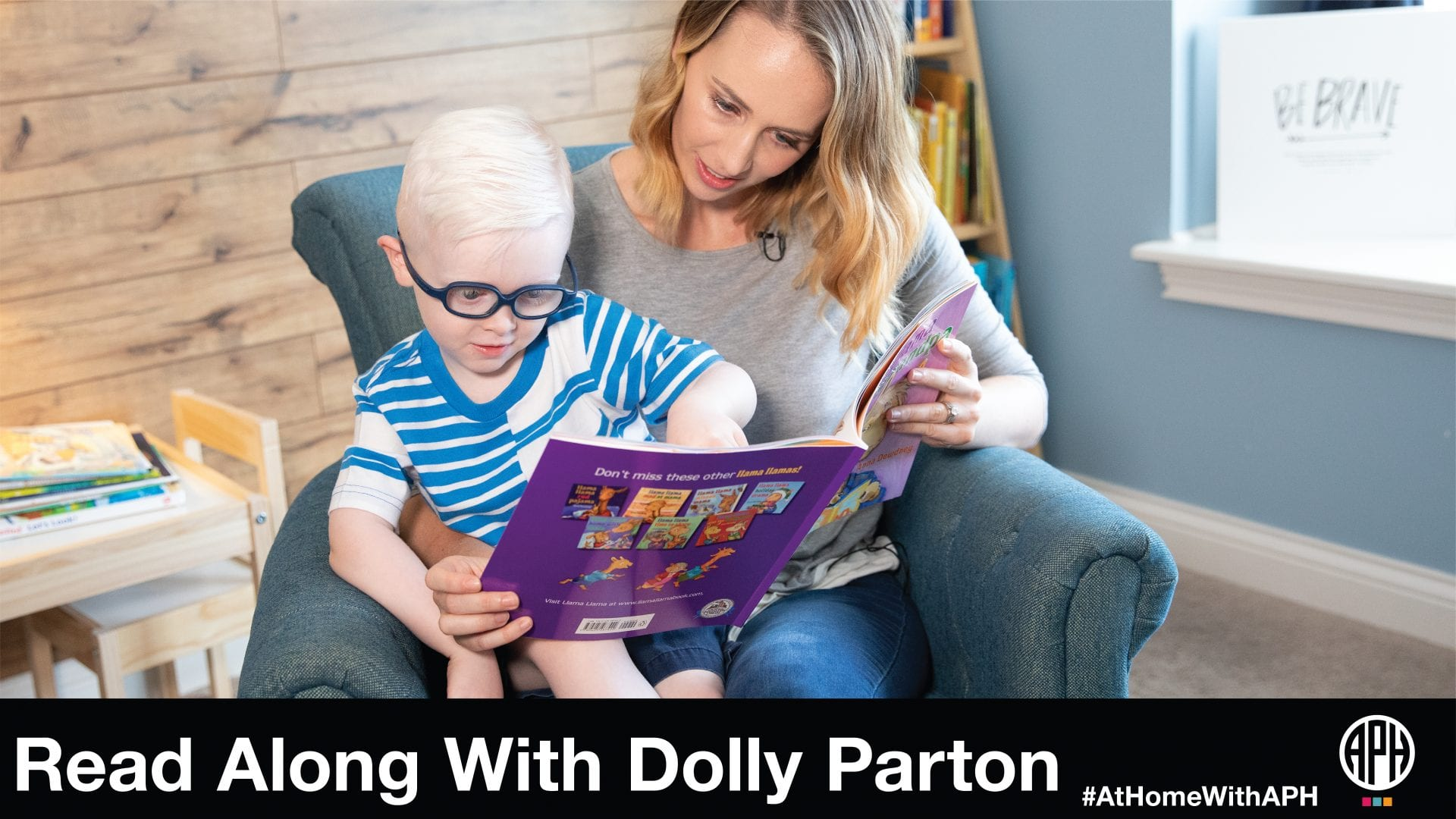 """a mother and young son in glasses sitting in an arm chair reading a book. text reads """"read along with Dolly Parton #AtHomeWithAPH"""""""
