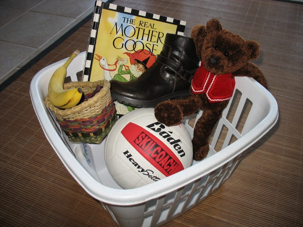 """a laundry basket filled with """"b"""" word items like bear and ball"""