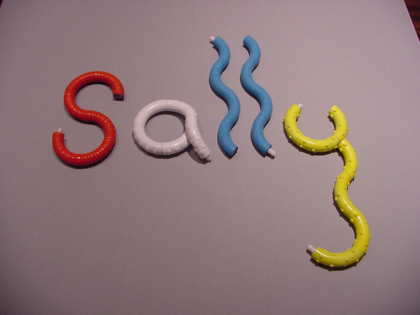 """photo of tangle toys spelling out the name """"sally"""" on a table top"""