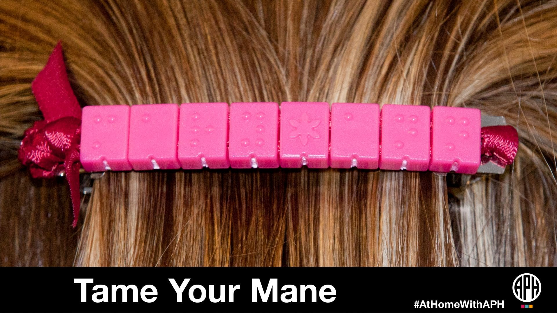 "a barrette made of pink braille beads in hair. text reads ""tame your mane #AtHomeWithAPH"""