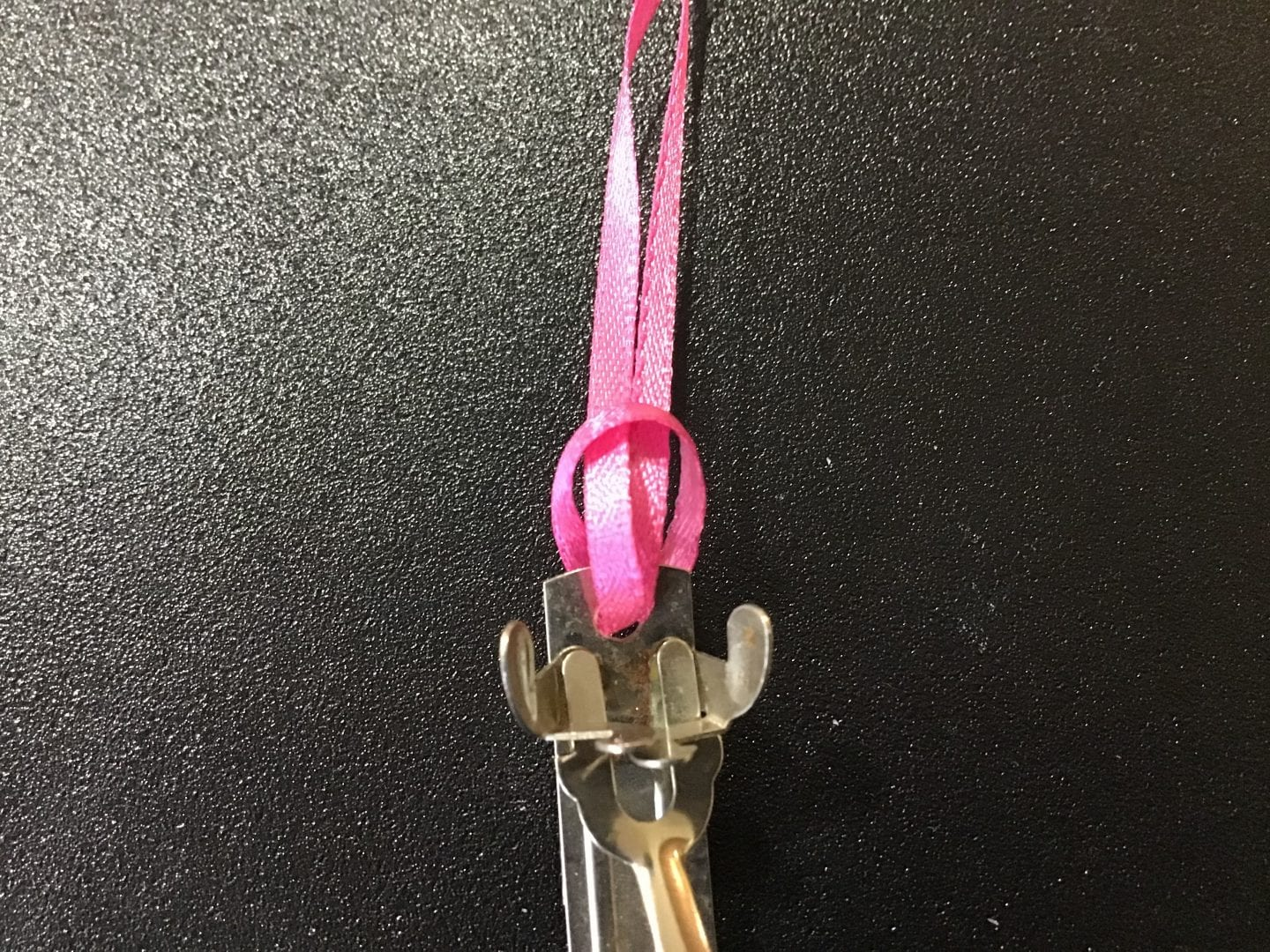 the two ends of the pink ribbon inserted through the open hole in the barrette and pulled through the loop at the other end of the ribbon