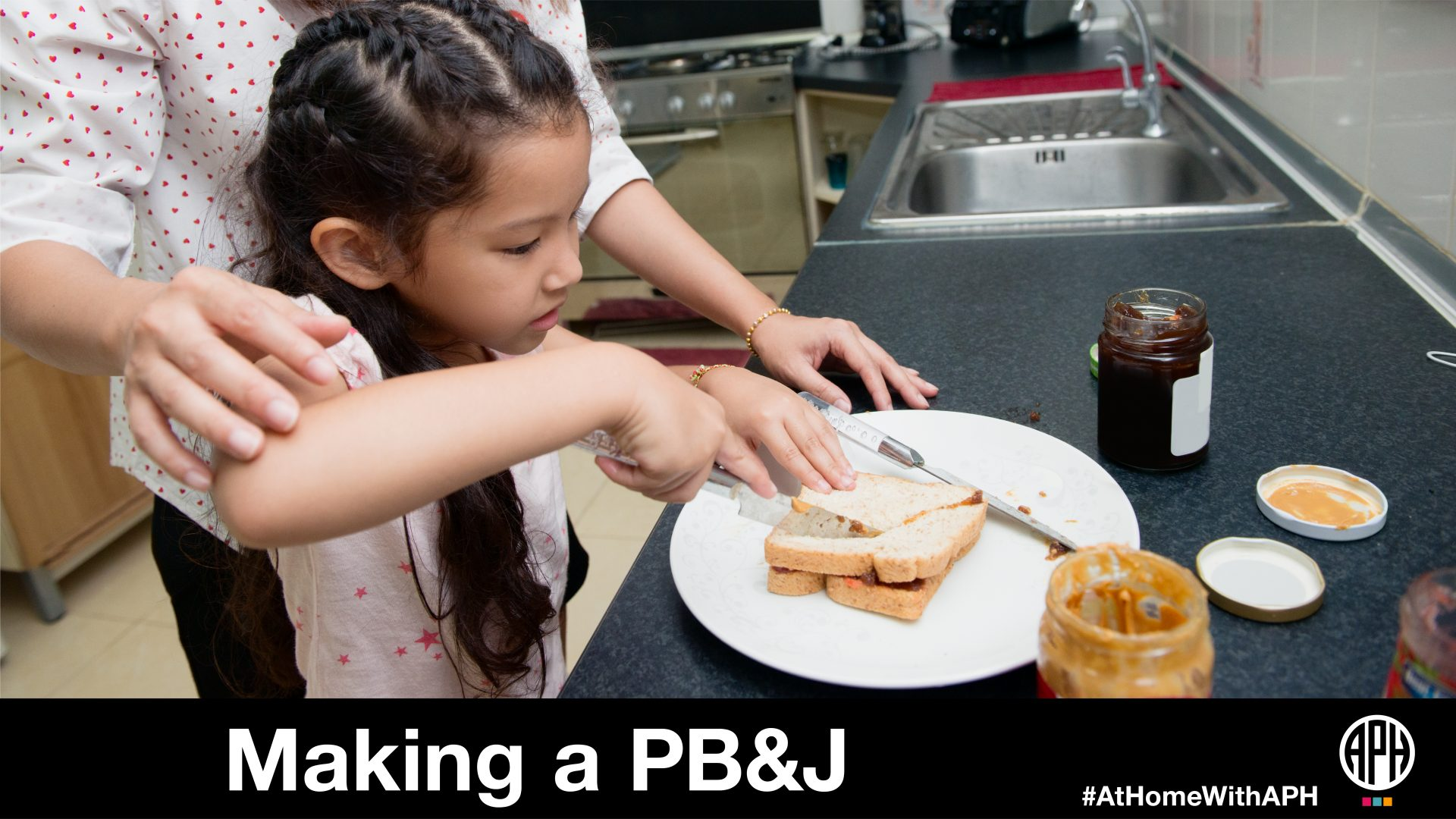 "a child cutting a peanut butter sandwich with a parents help. text reads ""Making a PB&J #AtHomeWithAPH"""