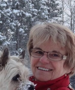 portrait photo of a woman in glasses standing outside in the snow holding a small blond dog