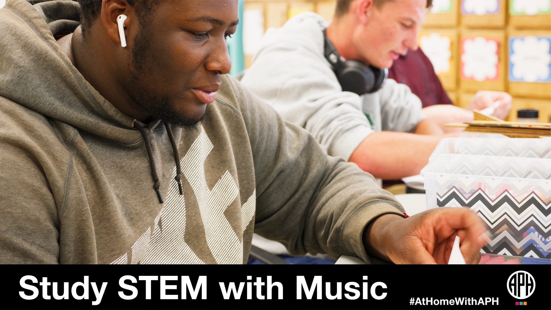 "two teenage students in the classroom doing work with headphones. text reads ""Studying STEM with Music #AtHomeWithAPH"""