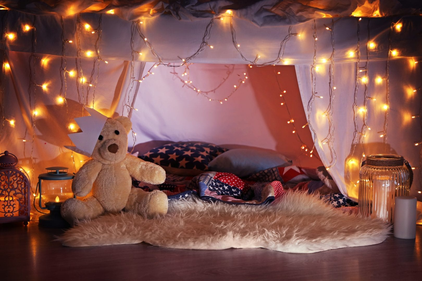 an indoor tent built out of sheets featuring, pillows, blankets, a teddy bear, and twinkle lights.