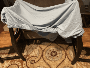 a fitted sheet stretched out over the tops of two dining room chairs, creating a covered space below