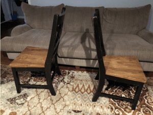 two dining room chairs back to back on a living room rug with a couple of feet between them