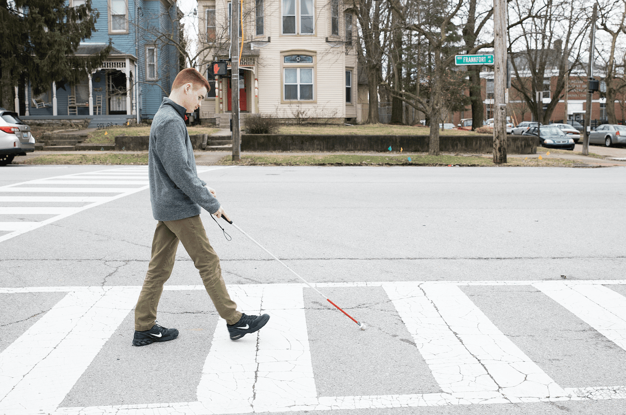 a teenage boy walking across the street at a crosswalk with a white cane