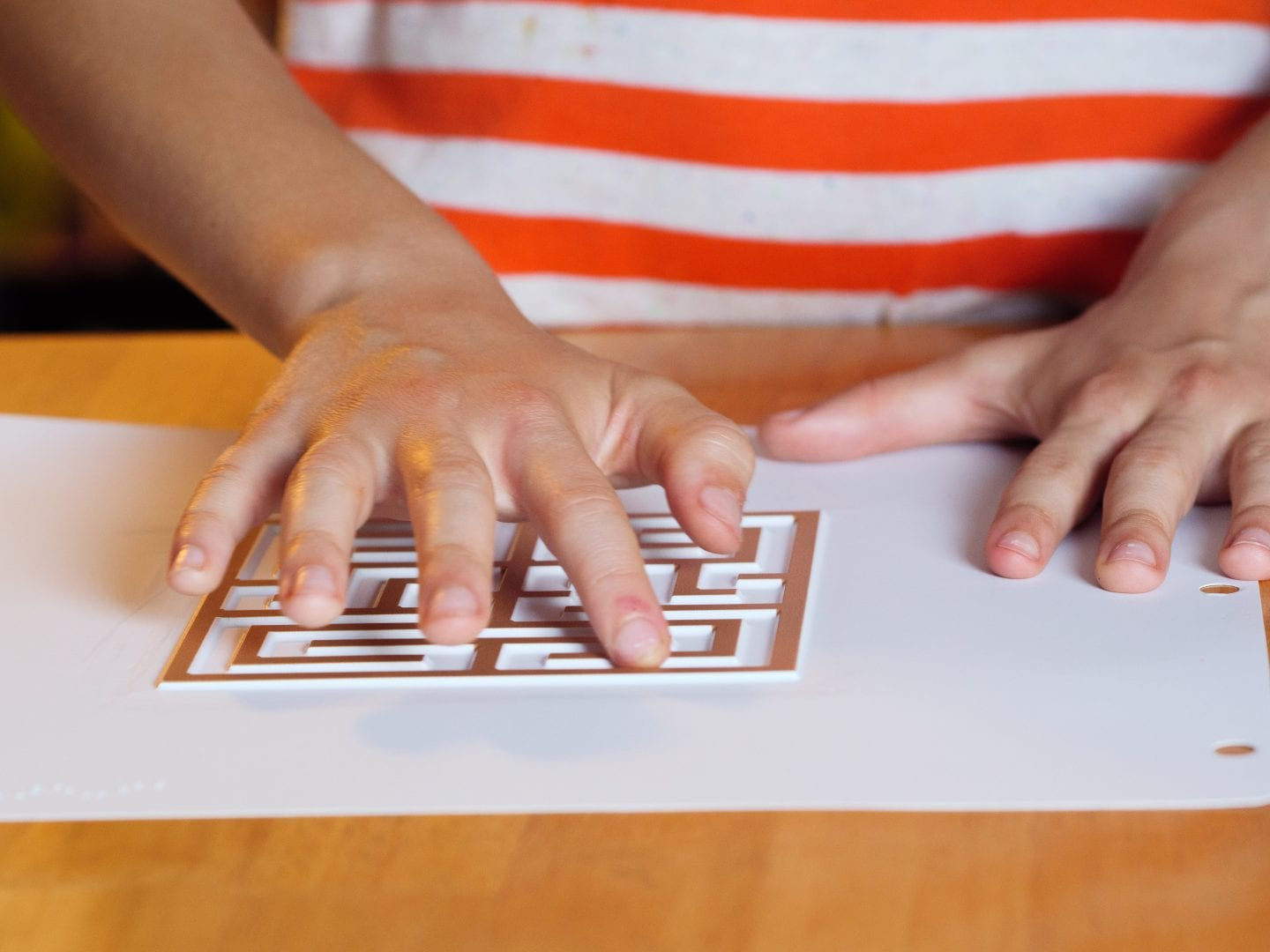 a child standing at a table with their one of their hands exploring a Finger Walks tactile labyrinth
