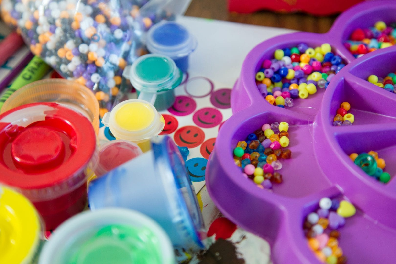 a variety of craft decorations including beads, paint, and stickers