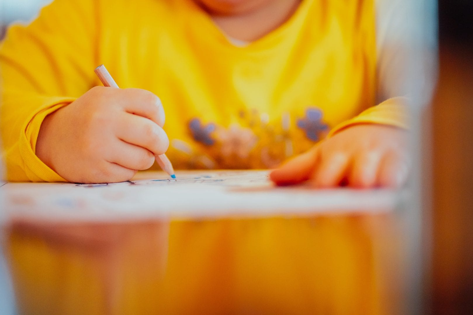 a kid in a yellow shirt coloring with a blue colored pencil