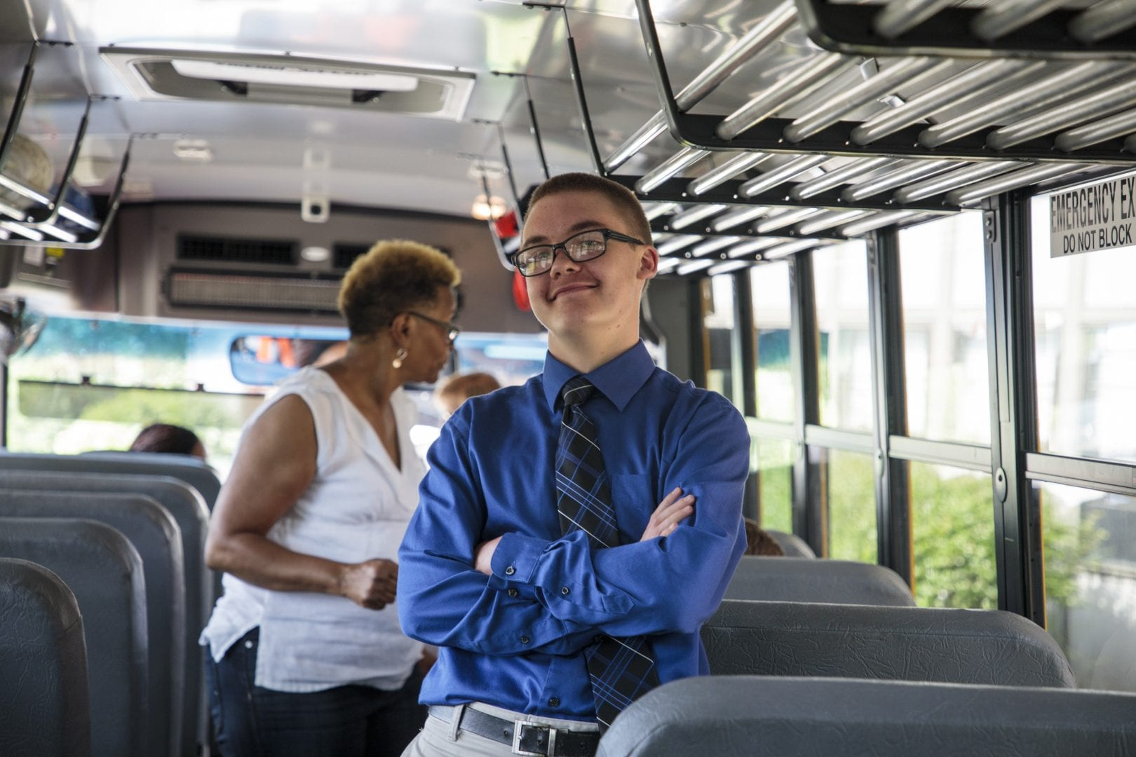 a boy on a school bus in a button up shirt and tie. His arms are crossed confidently.