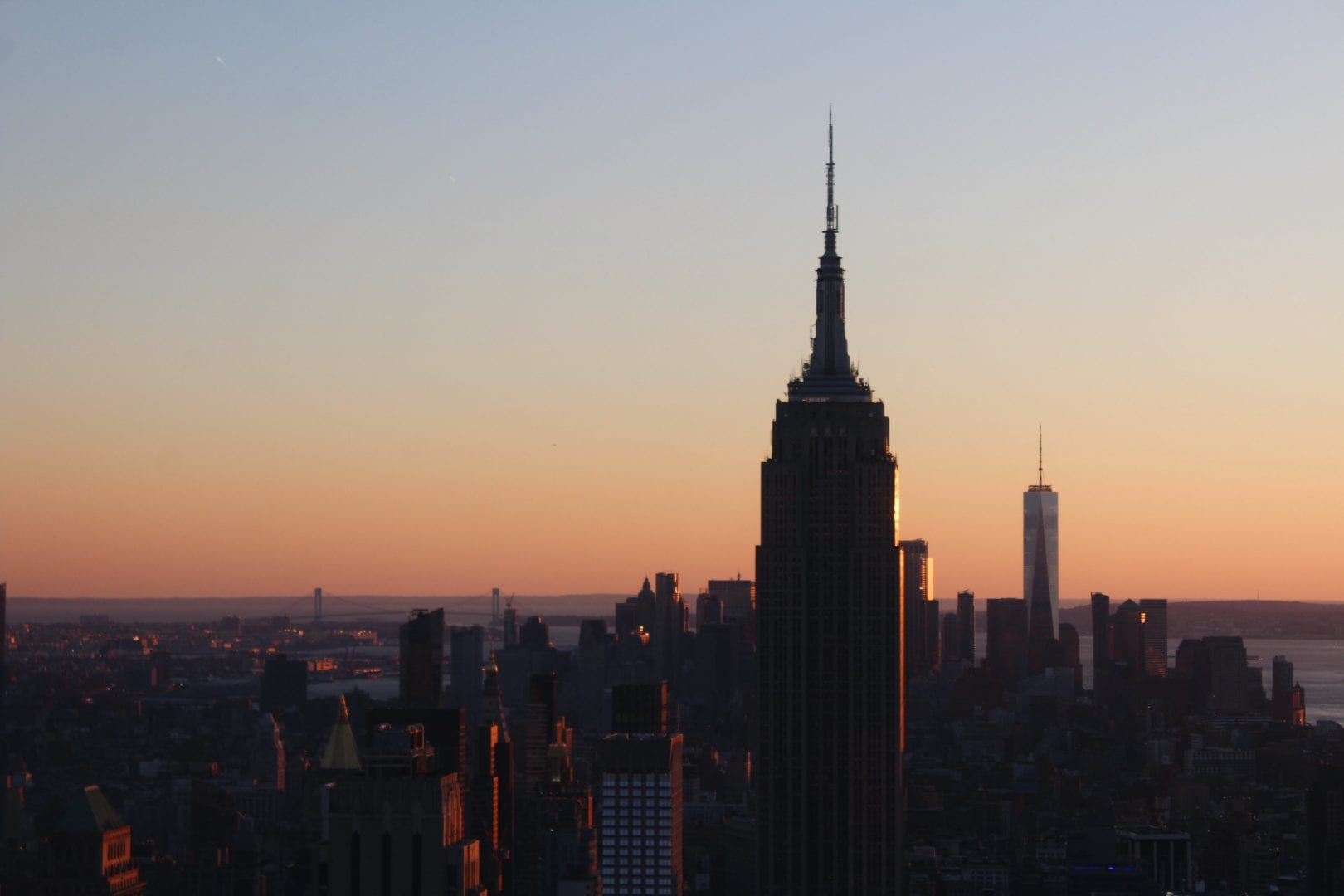 a skyline with a tower prominently shown at sunset