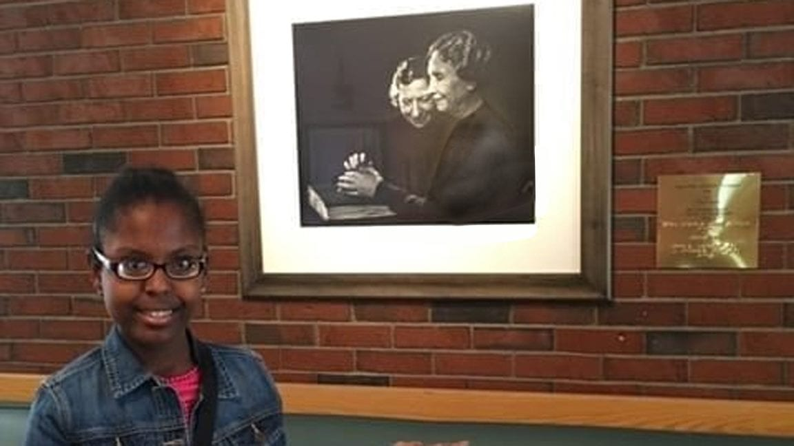A young woman, smiling, stands in front of a framed photograph of Anne Sullivan and Helen Keller.