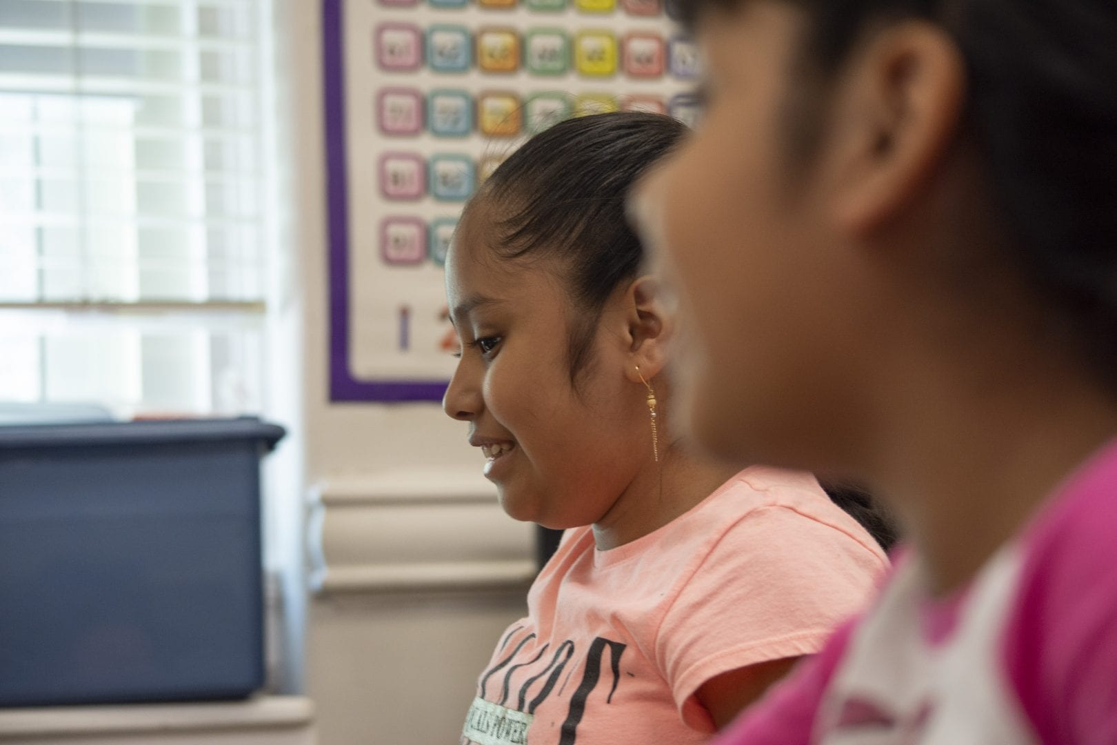 Two preteen girls in a classroom