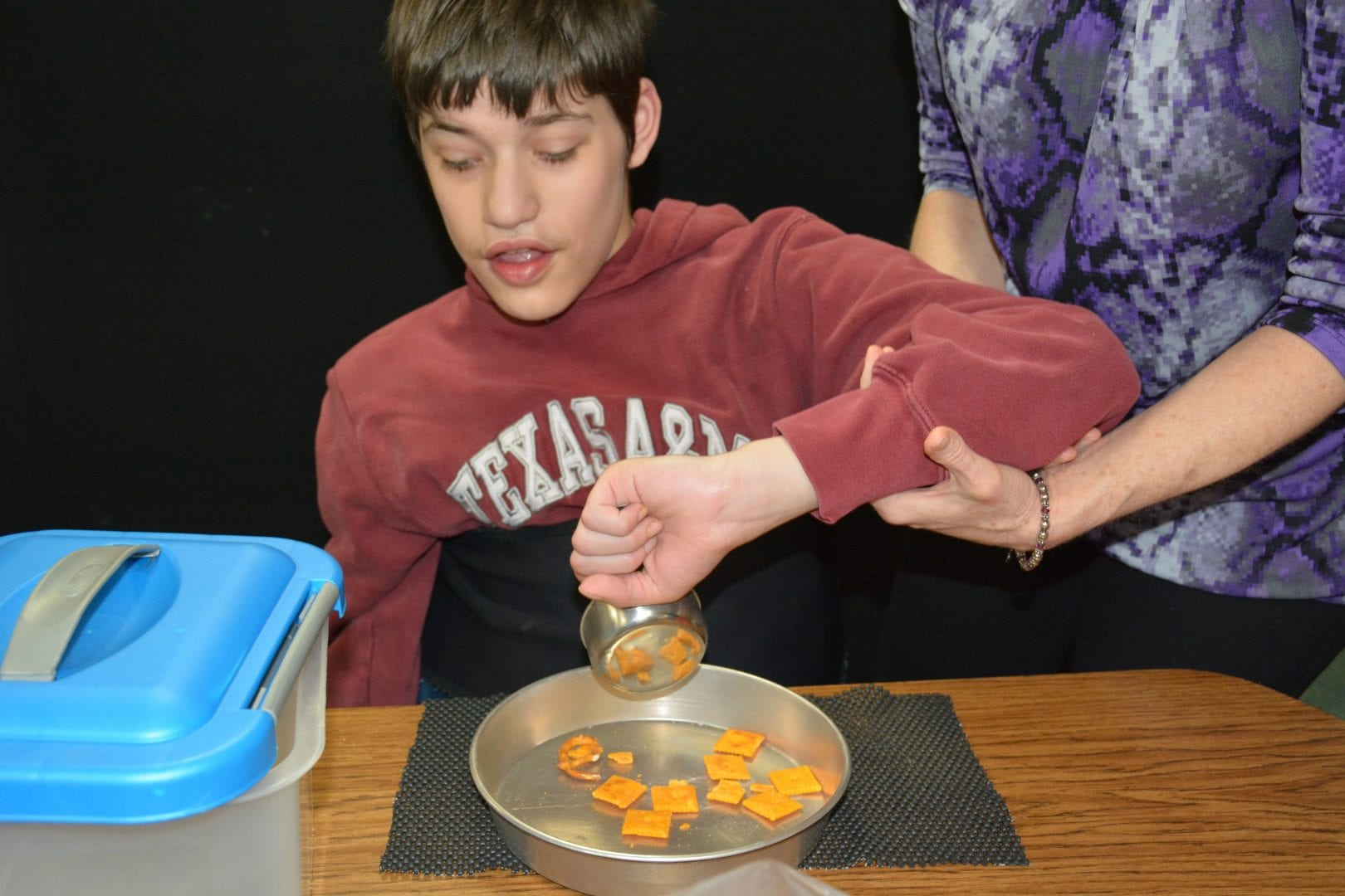 A teacher provides elbow support as a learner uses a measuring cup to pour his snack into a pan