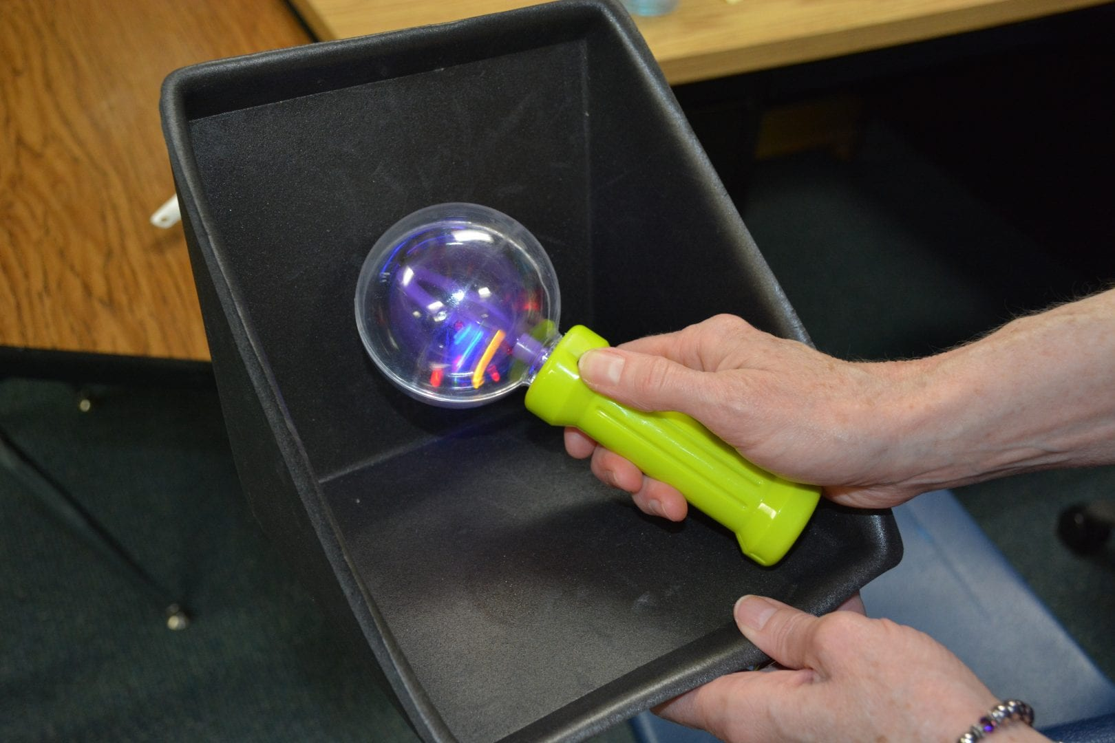 """A teacher presents the object symbol for """"Play Routine"""" in the learner's now container of his object calendar."""