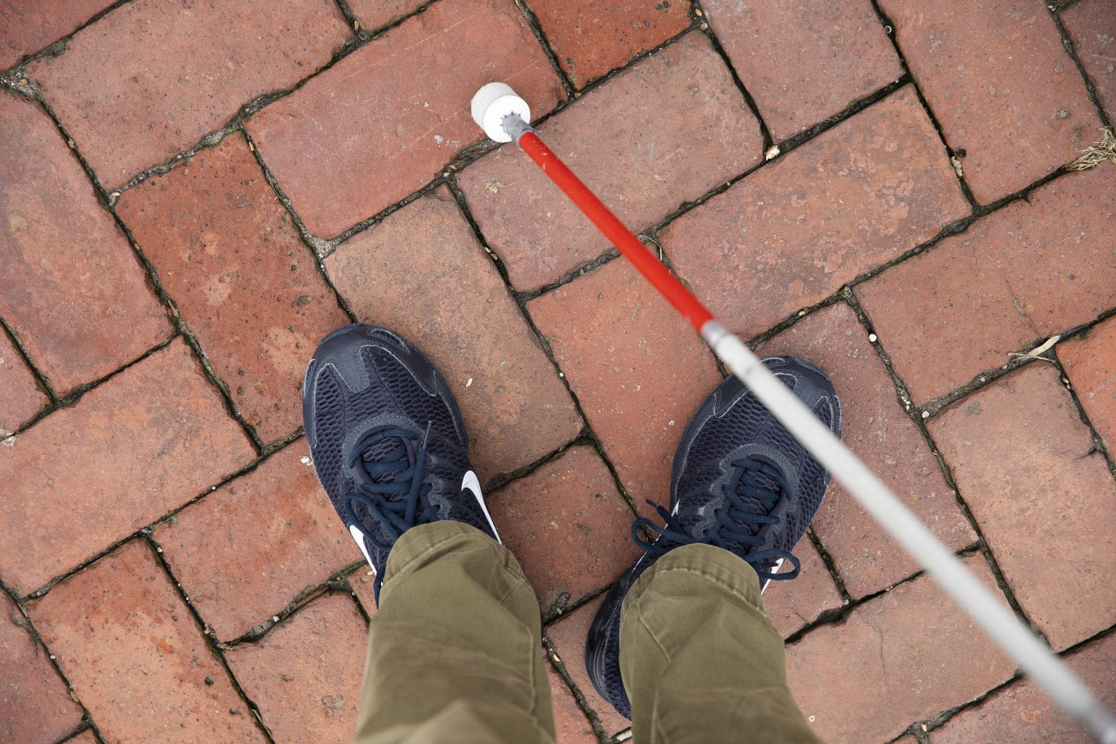 birds eye view of sneakered feet and a white cane on brick