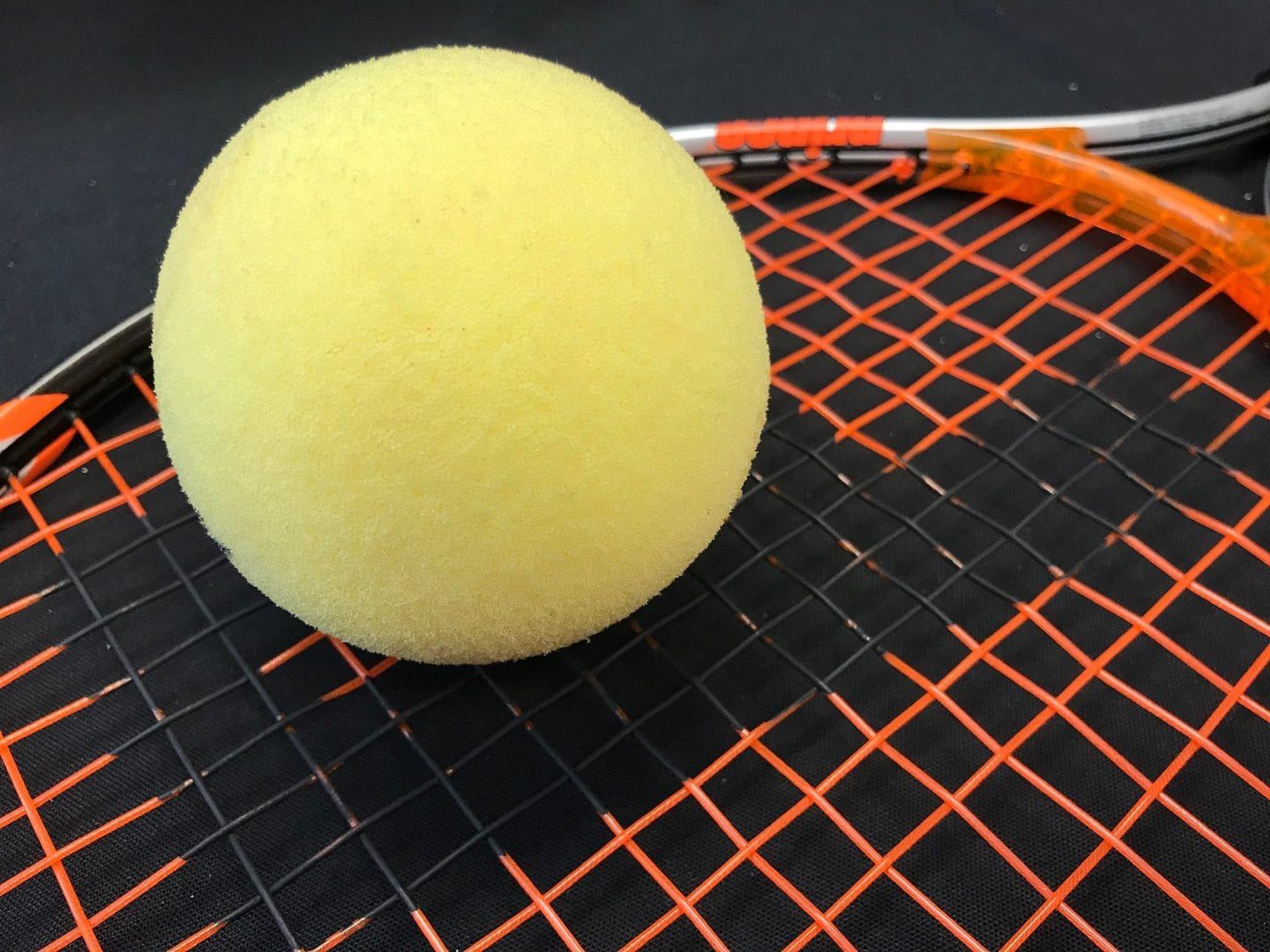 an aph tennis ball on a racket