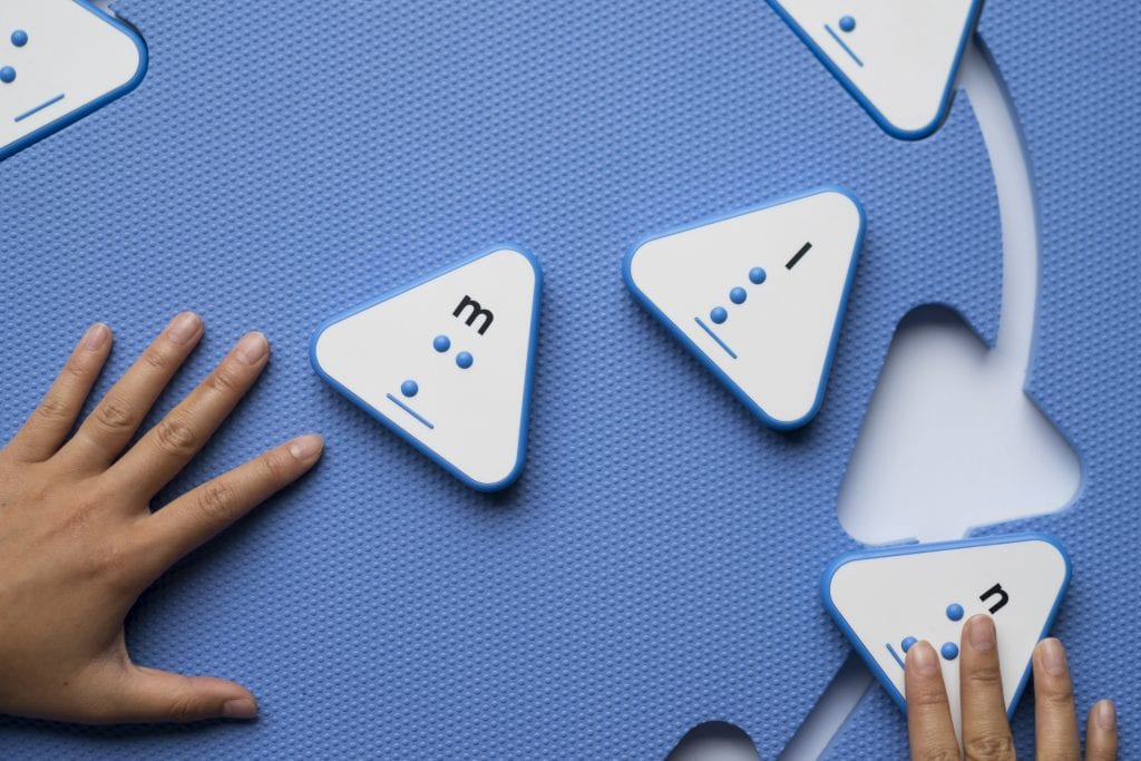 Two hands placing triangle print-braille tiles into the cutouts of the blue Reach & Match mat.