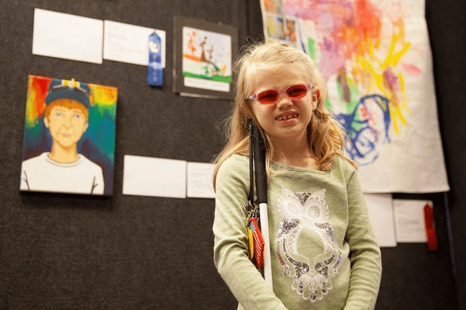 Young girl in pink sunglasses holding a white cane while standing in front of a wall of art