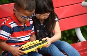 a little boy and girl, both wearing glasses, sit on a red bench and play with Braille Buzz together.