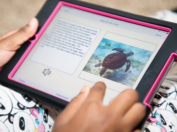an iPad displaying the AnimalWatch Vi Graphics app is held in a person's lap