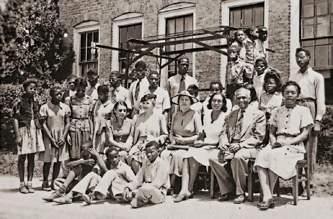 A group of Piney Woods School students and teachers in front of a brick building, with Helen Keller and her assistant Polly Thomson seated in the middle. Martha Foxx sits in the second row on the far left, wearing a light dress with dark buttons, her hands clasped in her lap.