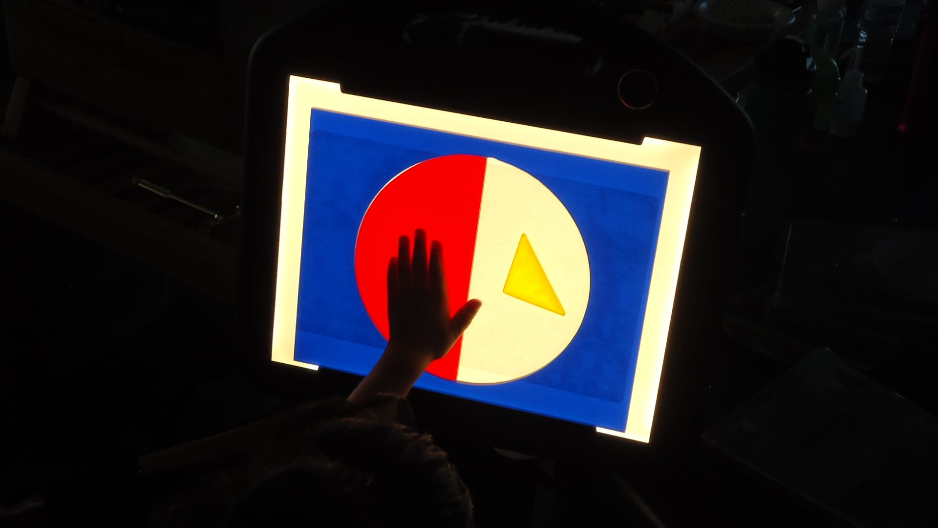 In a darkened room, a child's hand is touching blue plexiglass frame with a circle cut out. In the circle is a red plexiglass semi-circle and yellow triangle. The black case of the LED Mini-Lite Box disappears into the darkness.