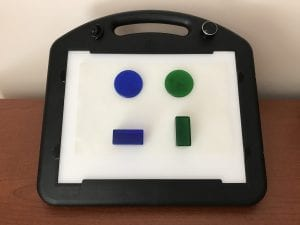 A blue circle and a green circle appear to float over a blue block and a green block respectively. All pieces are attached to the LED Mini-Lite Box surface with a sheet of Dycem