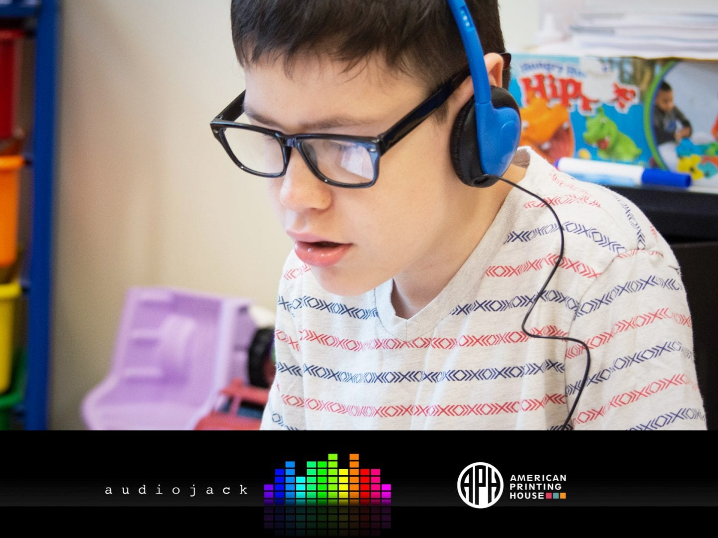 The Audiojack logo and APH logo beneath a photo of a boy engaged in listening to headphones