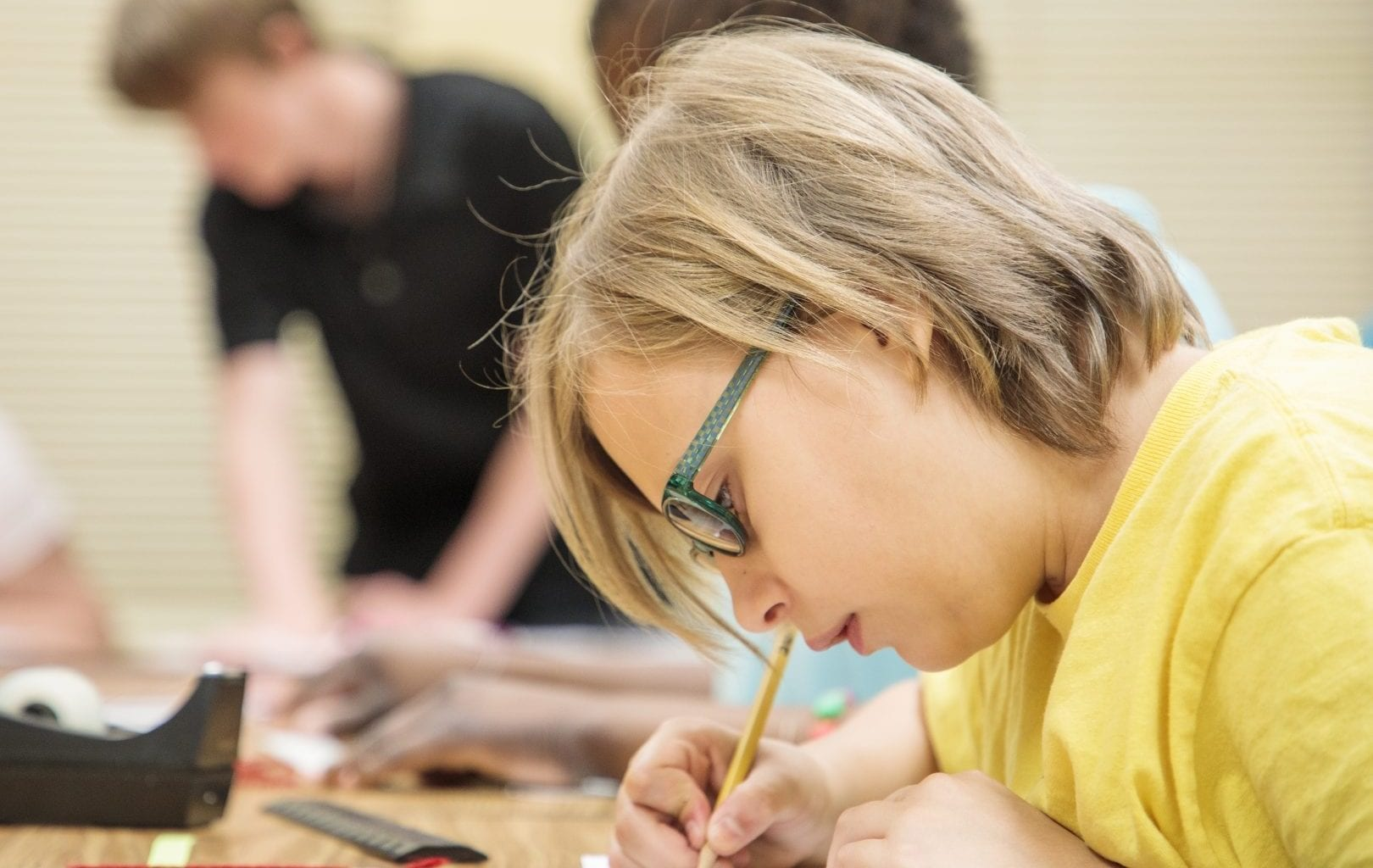 a student in glasses working at a desk with a pencil
