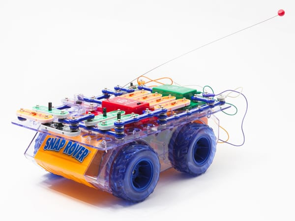 side view of RC Snap rover, a bread board covered in snap circuits pieces sitting on a frame with wheels.