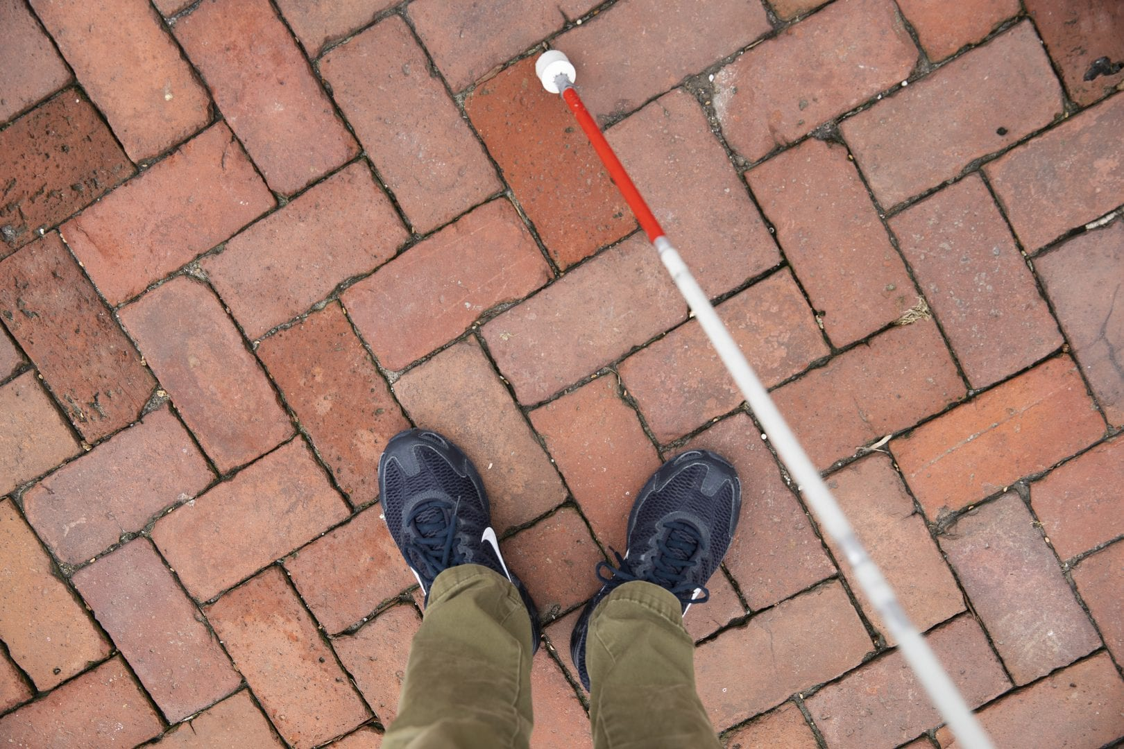 birds eye view of someone standing on a brick path with a white cane