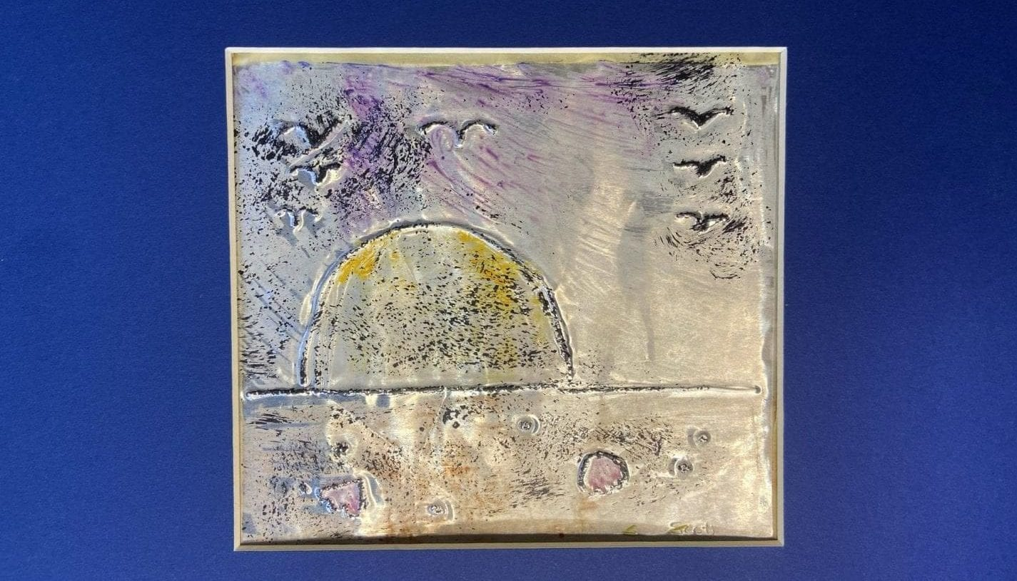 a square foil canvas on a blue background. The canvas is decorated with paint and a drawing in relief depicting a sunset on the water as seen from the beach with birds flying overhead