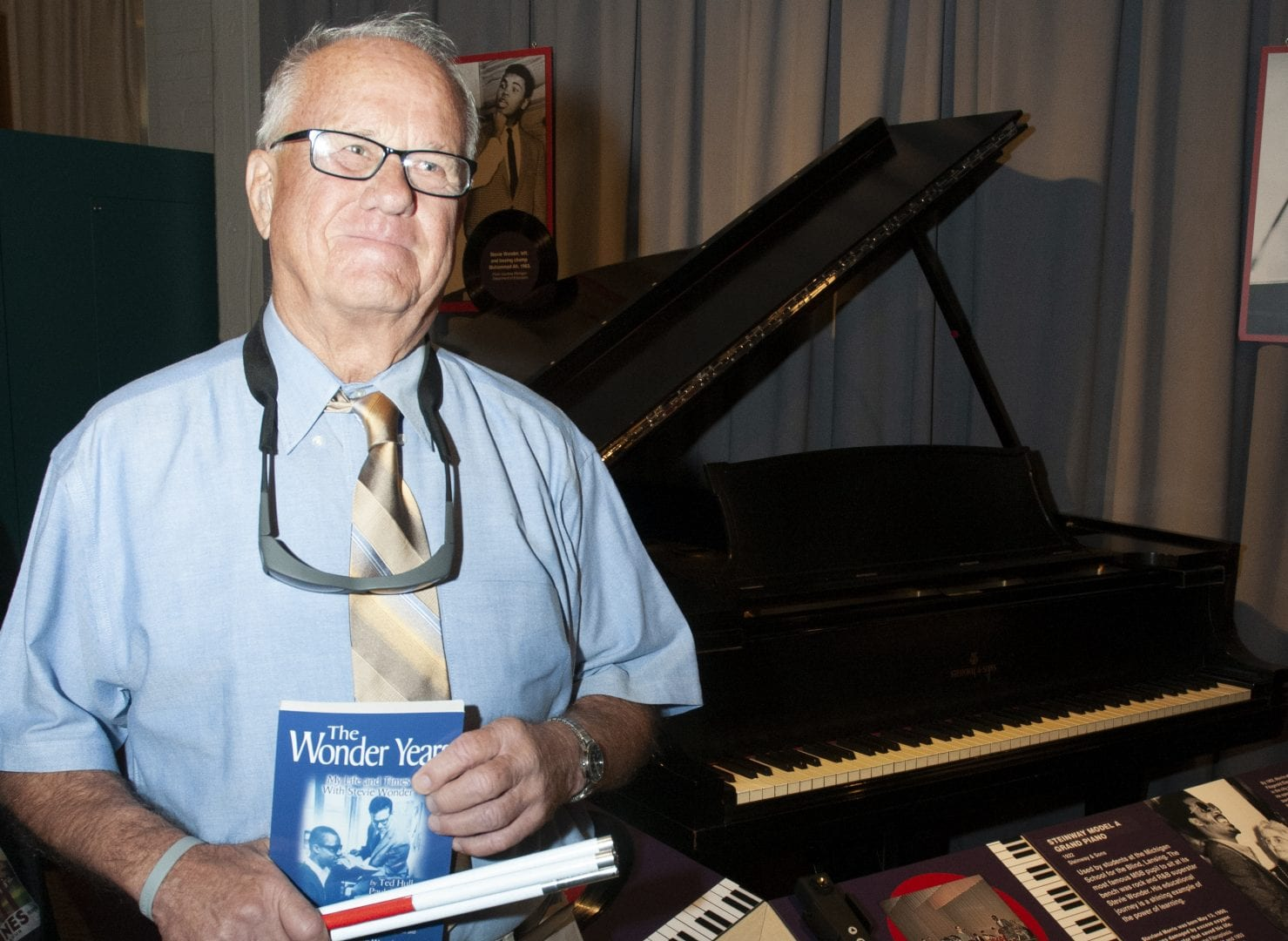 photo of a man standing with a folded white cane in front of a black piano on display in a museum