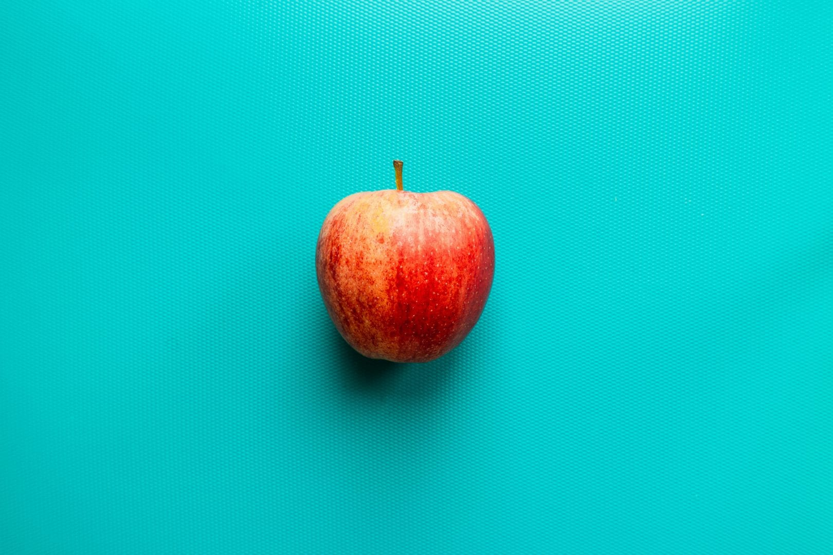 a red apple laying on a bright teal background