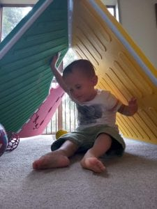Image: Reach & Match is put up in a configuration like a tent. A little boy who is blind is sitting under and smiling while touching the textures of the Reach & Match mats above him.