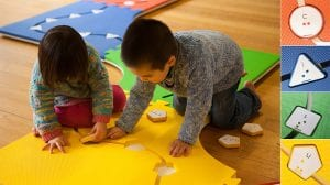 A little girl and little boy are playing on the path side of Reach & Match mats. There are circle, triangle, square, and pentagon tiles that can be put into the corresponding mats.