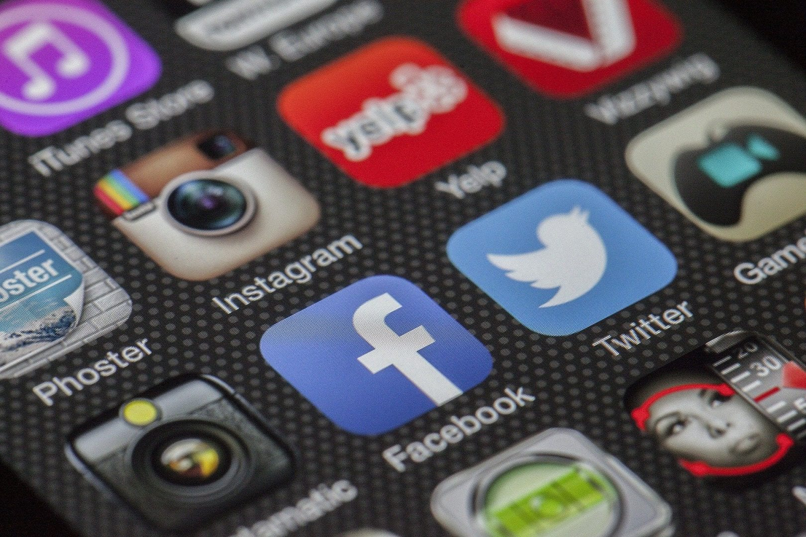 close up of a phone screen displaying a variety of apps including, Facebook, Twitter, and Instagram