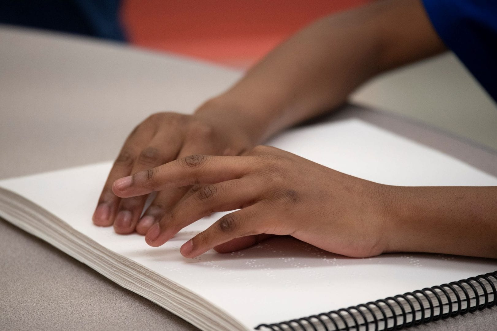 A close up of the hands of someone reading spiral bound braille