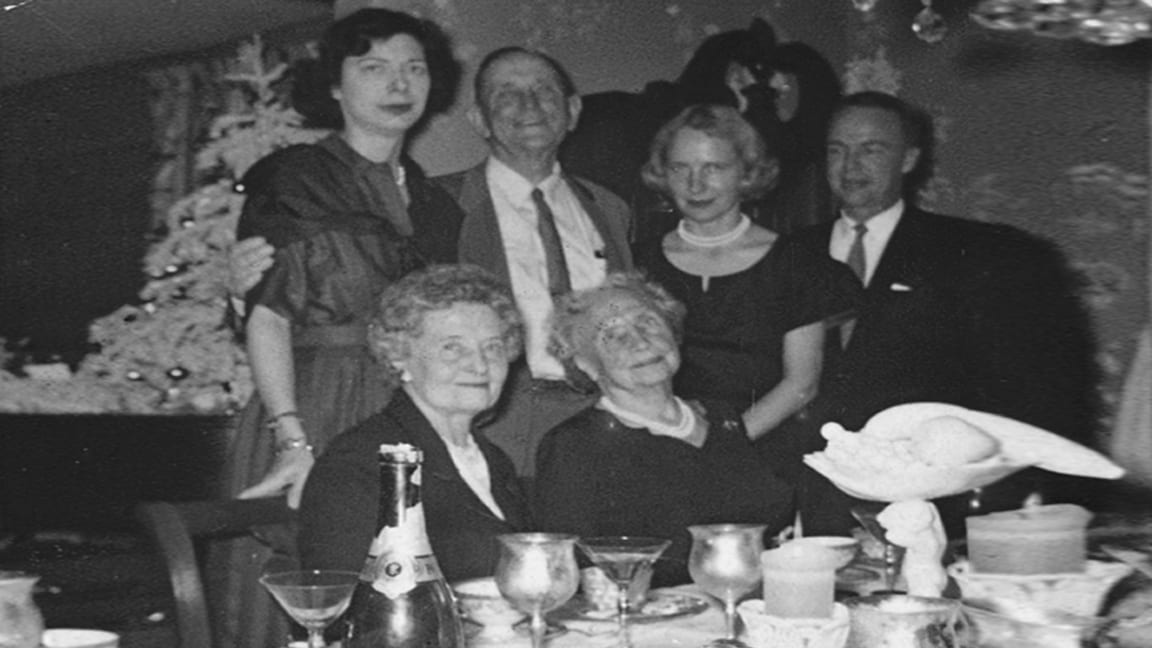 Helen is sitting at a dining table. She is wearing pearls and a dark-colored dress. Polly Thomson sits to her right; four others stand behind her, with arms around each other. A white Christmas tree decorated with ball-shaped ornaments is in the background. The table is crowded with napkins, candles, coffee cups, long-stemmed glasses, and a bottle of champagne.