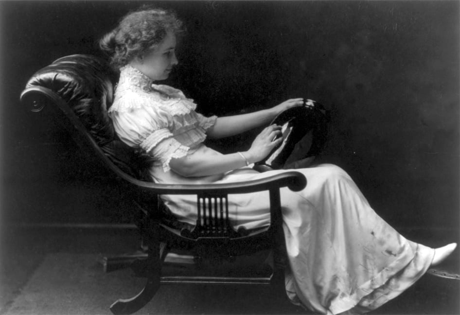 Helen sitting back in a chair with a reclined back. The arms are wood and the seat and backrest are plushly stuffed leather