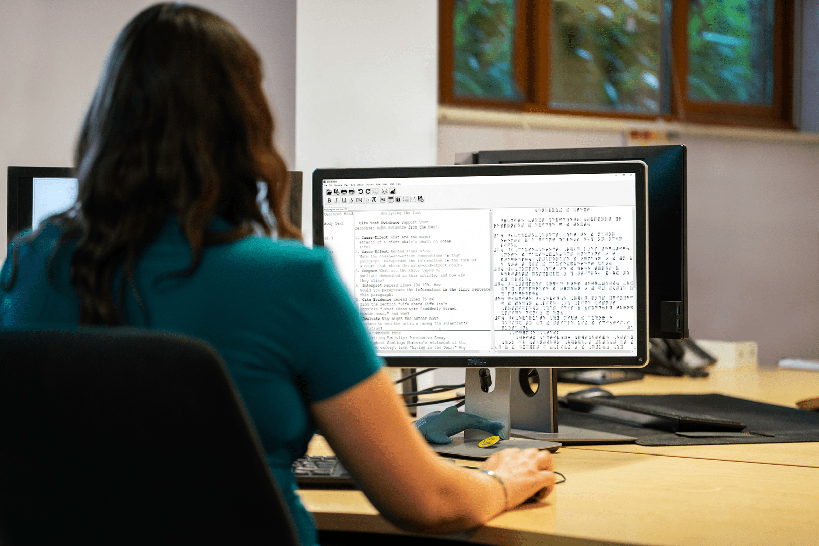 image of a woman sitting at a desk using brailleblaster on a computer