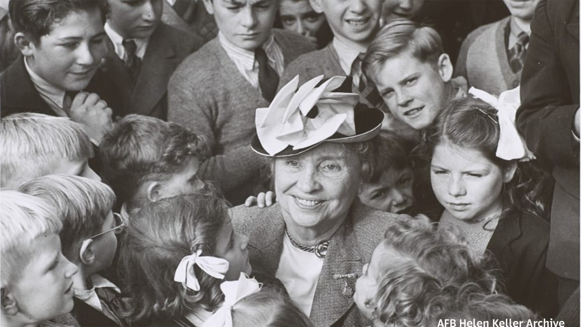 Helen as an older adult in a small hat is smiling while surrounded by a big group of children