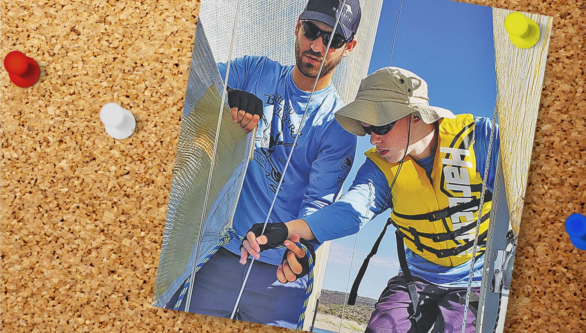 photo pinned to a cork board. photo shows a man in a hat and sunglasses hellping a boy in a lifejacket on a sail boat.