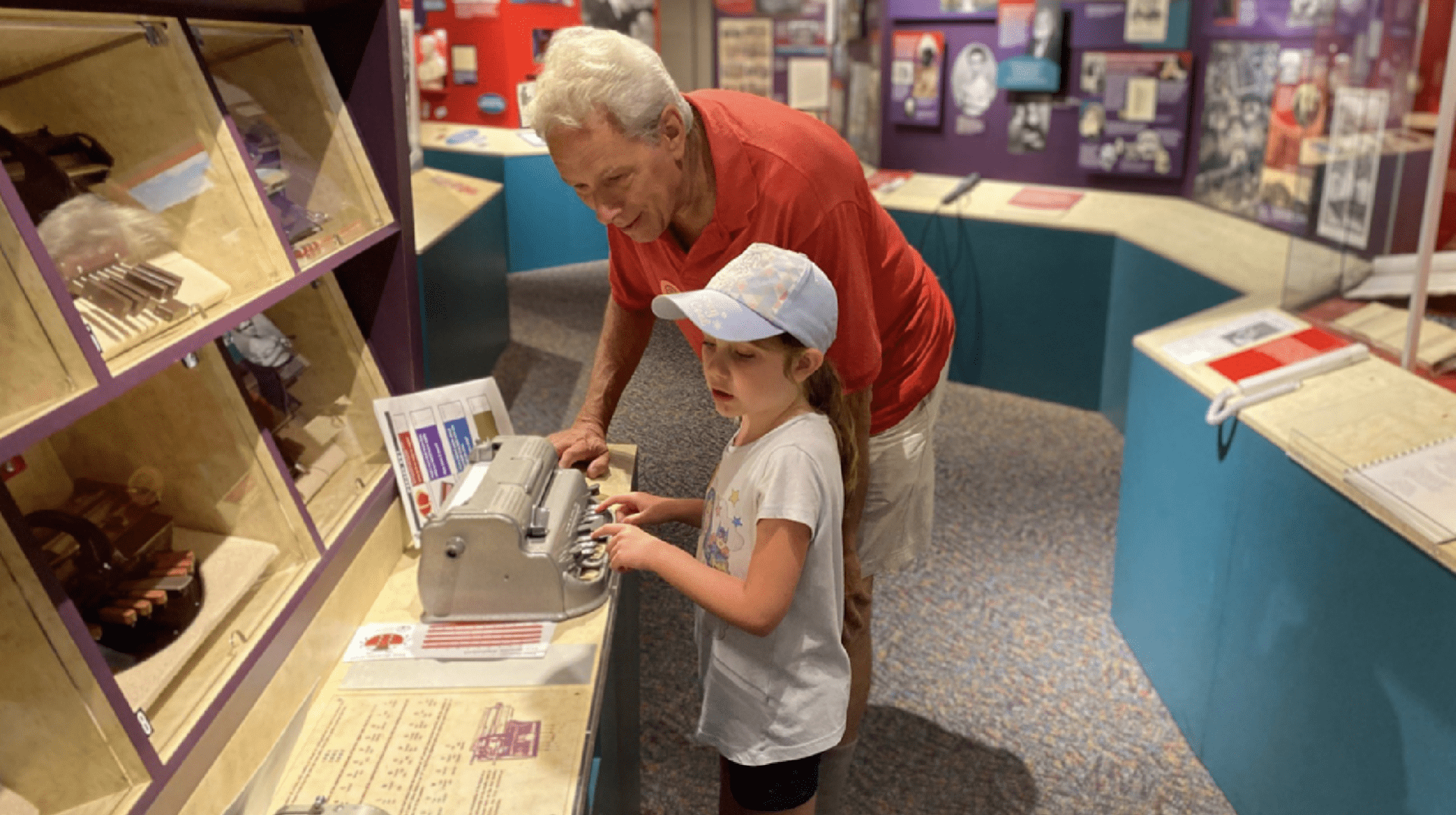 An older man watches intently as a young girl wearing a baseball hat demonstrates how to use the braillewriter.