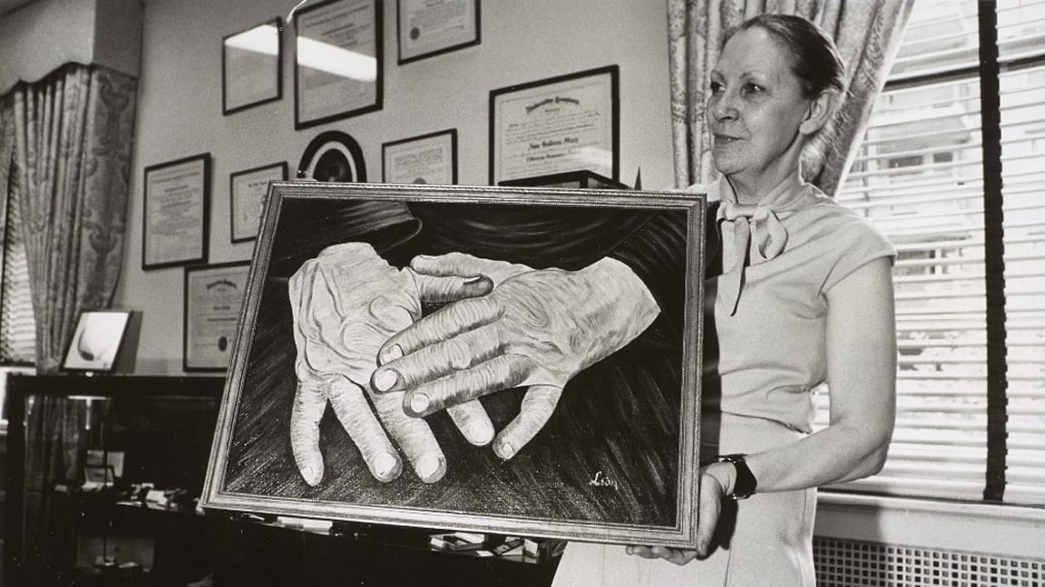 A woman holds a large painting depicting two hands, the left hand resting on the right. The woman wears a blouse with a bow and her hair has been pulled back into a bun. On the wall behind her are various framed documents.
